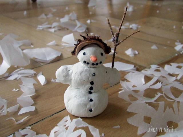 Sněhulák z modelovací hmoty mezi papírovými vločkami